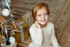 Aanbiddelijk weinig blond meisje met blauwe ogen die en a glimlachen houden Royalty-vrije Stock Afbeeldingen