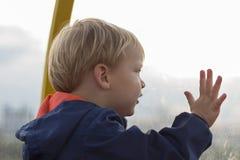 Aanbiddelijk weinig blonde zitting van de jong geitjejongen dichtbij venster en buiten het kijken royalty-vrije stock fotografie