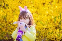 Aanbiddelijk weinig grappig stuk speelgoed van het de holdingskonijn van het konijntjesmeisje in de tuin van de de lentebloesem stock afbeeldingen