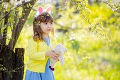 Aanbiddelijk weinig grappig stuk speelgoed van het de holdingskonijn van het konijntjesmeisje in de tuin van de de lentebloesem stock afbeelding