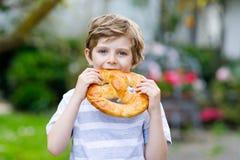 Aanbiddelijk weinig jong geitjejongen die reusachtige grote Beierse Duitse pretzel eten royalty-vrije stock foto's