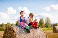 Aanbiddelijk weinig jong geitjejongen en meisje in traditionele Beierse kostuums op tarwegebied op hooistapel royalty-vrije stock foto