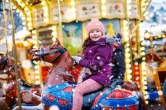 Aanbiddelijk weinig jong geitjemeisje die op een carrouselpaard bij Kerstmis funfair of markt berijden, in openlucht stock fotografie