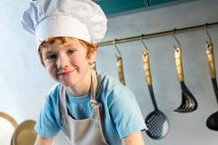 aanbiddelijk weinig jongen in chef-kokhoed en schort die bij camera glimlachen royalty-vrije stock afbeeldingen