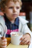 Aanbiddelijk weinig jongen die bevroren yoghurtroomijs in koffie eten Stock Foto's