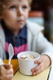 Aanbiddelijk weinig jongen die bevroren yoghurtroomijs in koffie eten Stock Foto