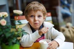 Aanbiddelijk weinig jongen die bevroren yoghurtroomijs in koffie eten Stock Afbeeldingen