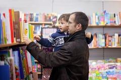 Aanbiddelijk weinig jongen, die in een boekhandel zitten Stock Foto
