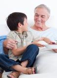 Aanbiddelijk weinig jongen die zijn grootvader behandelt stock foto