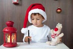 Aanbiddelijk weinig jongen, het schrijven brief aan Kerstman Royalty-vrije Stock Afbeeldingen