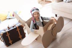 Aanbiddelijk weinig kind die met kartonvliegtuig spelen royalty-vrije stock afbeelding