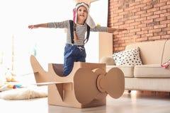 Aanbiddelijk weinig kind die met kartonvliegtuig spelen stock afbeelding
