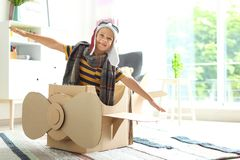 Aanbiddelijk weinig kind die met kartonvliegtuig spelen royalty-vrije stock fotografie