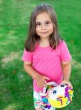 Aanbiddelijk weinig kindmeisje met een pop in haar handen die in de tuin spelen stock foto's