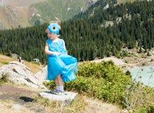 Aanbiddelijk weinig kindmeisje op gras op weide De zomer groene aard Stock Fotografie
