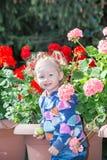 Aanbiddelijk weinig kindmeisje in park dichtbij bloembed in de zomerdag Stock Afbeelding