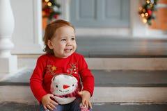 Aanbiddelijk weinig meisje van het blondemeisje in een sweater met een sneeuw Royalty-vrije Stock Fotografie