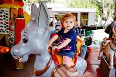 Aanbiddelijk weinig peutermeisje die op dier op rotondecarrousel berijden in pretpark Gelukkig gezond babykind die hebben stock afbeeldingen