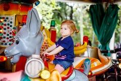 Aanbiddelijk weinig peutermeisje die op dier op rotondecarrousel berijden in pretpark Gelukkig gezond babykind die hebben stock foto