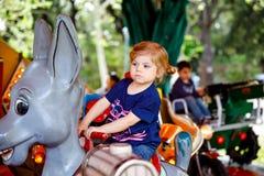 Aanbiddelijk weinig peutermeisje die op dier op rotondecarrousel berijden in pretpark Gelukkig gezond babykind die hebben royalty-vrije stock afbeeldingen