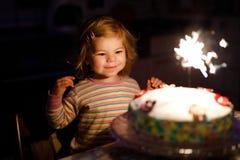 Aanbiddelijk weinig peutermeisje het vieren tweede verjaardag Babykind die marshmellows decoratie op eigengemaakte cake eten stock foto