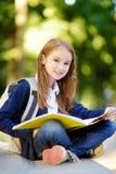 Aanbiddelijk weinig schoolmeisje die in openlucht op heldere de herfstdag bestuderen Jonge student die haar thuiswerk doen Onderw Royalty-vrije Stock Foto