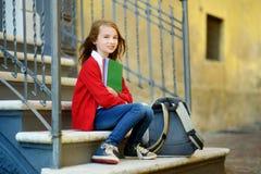 Aanbiddelijk weinig schoolmeisje die in openlucht op heldere de herfstdag bestuderen Jonge student die haar thuiswerk doen Onderw Royalty-vrije Stock Afbeeldingen