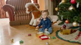 Aanbiddelijke 1 éénjarige babyjongen het spelen onder Kerstboom bij woonkamer stock videobeelden