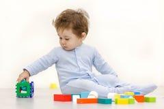 Aanbiddelijke éénjarigenkind het spelen met stuk speelgoed kubussen Stock Foto's