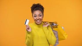 Aanbiddelijke Afro-Amerikaanse het krediet van de dameholding kar en het winkelen shopaholic zakken, stock videobeelden