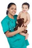 Aanbiddelijke arts met een baby in haar wapens stock foto