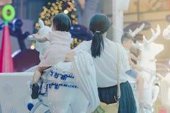 Aanbiddelijke Aziaat weinig jong geitjemeisje die op vrolijk berijden gaat om carous stock foto's