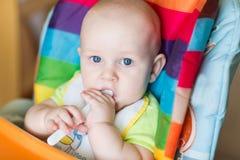 Aanbiddelijke baby die als hoge voorzitter eten Royalty-vrije Stock Foto