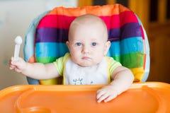 Aanbiddelijke baby die als hoge voorzitter eten Royalty-vrije Stock Foto's