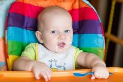 Aanbiddelijke baby die als hoge voorzitter eten Stock Foto