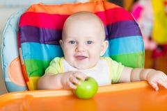 Aanbiddelijke baby die als hoge voorzitter eten Stock Afbeelding