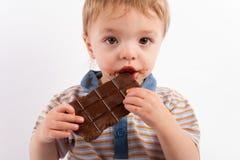 Aanbiddelijke baby die een chocoladereep eten Royalty-vrije Stock Foto's