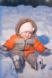 Aanbiddelijke baby die neer van sneeuwheuvel glijdt stock afbeelding