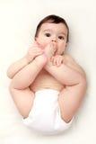 Aanbiddelijke baby die zijn tenen zuigt Royalty-vrije Stock Foto's