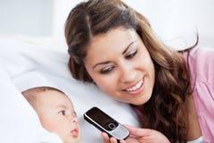 Aanbiddelijke baby met zijn moeder die een cellphone houdt royalty-vrije stock afbeelding