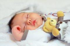 Aanbiddelijke baby pasgeboren slaap met stuk speelgoed stock afbeelding