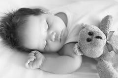 Aanbiddelijke baby, vreedzaam in slaap in voederbak naast een teddybeer op een koele middag in zwart-wit Royalty-vrije Stock Foto's