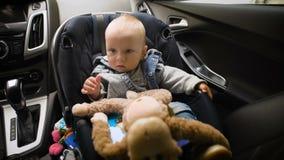 Aanbiddelijke babyjongen in de zetel van de veiligheidsauto stock footage