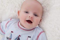 Aanbiddelijke babyjongen die bij bont het algemene glimlachen ligt Stock Foto's