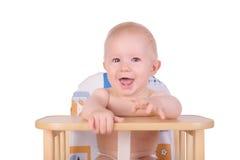 Aanbiddelijke babyjongen die op voedsel zijn stoel wachten Stock Afbeeldingen
