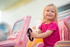 Aanbiddelijke babyrit op stuk speelgoed auto in wandelgalerij Royalty-vrije Stock Foto's