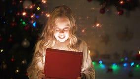 Aanbiddelijke blonde meisje het openen giftdoos, magische Kerstmisatmosfeer, het gloeien effect stock videobeelden