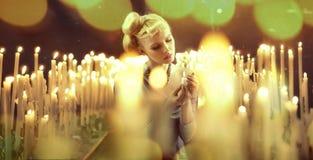 Aanbiddelijke vrouw onder milions van kaarsen Stock Afbeeldingen