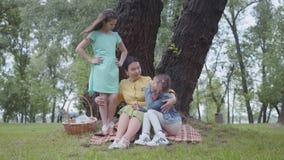 Aanbiddelijke elegante hogere vrouwenzitting op de deken onder de boom in het park die met twee leuke kleindochters spreken stock footage
