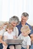 Aanbiddelijke familie die laptop bekijkt Stock Foto
